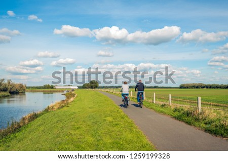 Two unidentified people cycle on a cycle path at the top of a dike along a narrow river at the Dutch National Park De Biesbosch in the province of Noord-Brabant. #1259199328