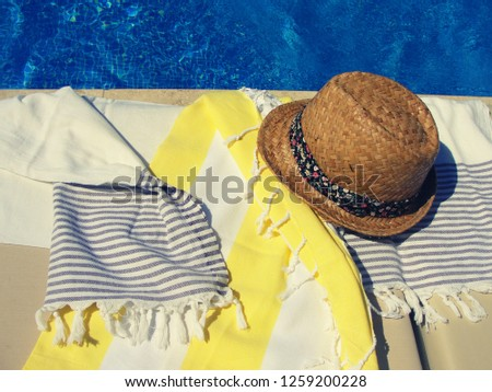 Straw summer hat with ribbon and cotton towels on a sunbed near the swimming pool. Bright sunny summer vacation day, filtered image, contrast filter effect #1259200228