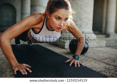 Close up of a woman doing fitness training with a medicine ball by her side. Fitness woman doing push ups on a training mat. #1259254519
