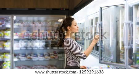 Women choosing a dairy products at supermarket. Reading product information #1259291638