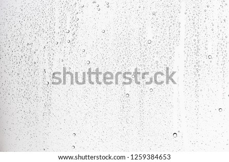 white isolated background water drops on the glass / wet window glass with splashes and drops of water and lime, texture autumn background Royalty-Free Stock Photo #1259384653
