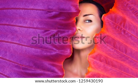 Beautiful Woman face with Natural  make-up on a tropical Ultra Violet leaf background in the jungle. Sexy beautiful woman behind the colorful leaves. Pure cosmetic and wellness art concept. Neon  #1259430190