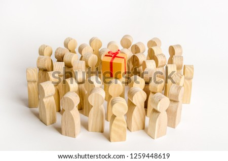 A large group of people surrounds a box with a present. The concept of choosing a good gift, limited number, all sold out. A gift for the community. Birthday party, New Year and Christmas. collective #1259448619