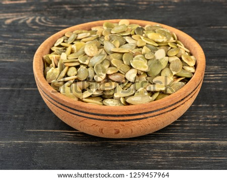 Pumpkin seeds without shell in a bowl on wooden background #1259457964