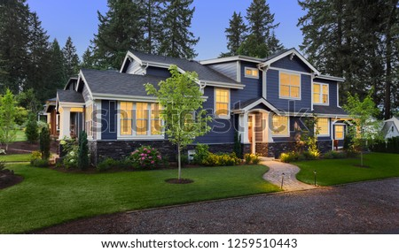 Beautiful Home Exterior at Twilight: New House with Beautiful Yard and Landscaping with Glowing Interior Lights #1259510443