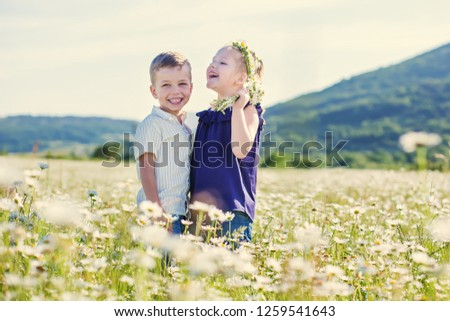 Lovely little children in the field of daisies. #1259541643