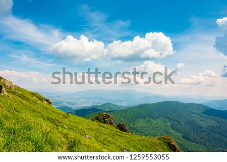 rock on grassy slope of a mountain. beautiful view from the top of a hill. wonderful summer landscape on a sunny day. beautiful clouds on a blue sky #1259553055