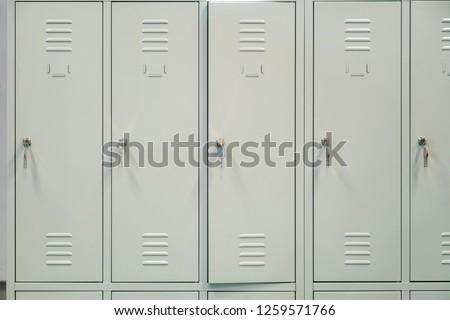 A row of grey metal school lockers with keys in the doors #1259571766