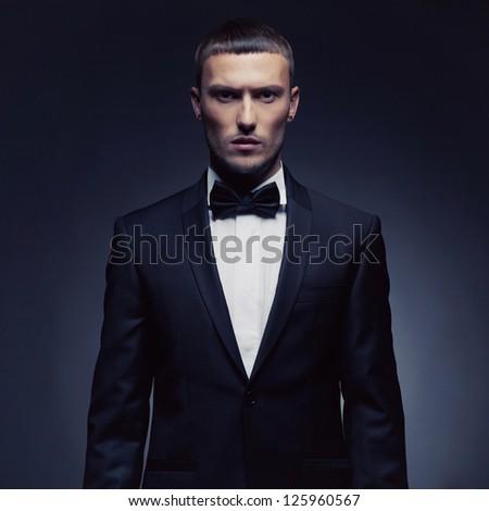 Portrait of handsome stylish man in elegant black suit #125960567