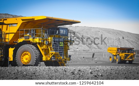 Spot color trucks, two large yellow truck used in a modern coal mine in Queensland, Australia. Trucks transports coal from open cast mine. Fossil fuel industry, Environmental challenge. Logos removed. #1259642104