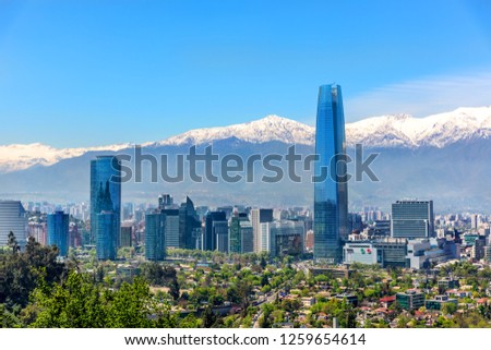 Plenty of business buildings in Santiago del Chile with trees in the foreground and the Andes mountains in the background #1259654614