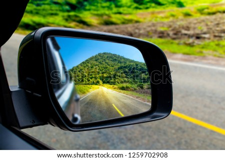 Landscape in the sideview mirror of a car , on road countryside. - Image #1259702908