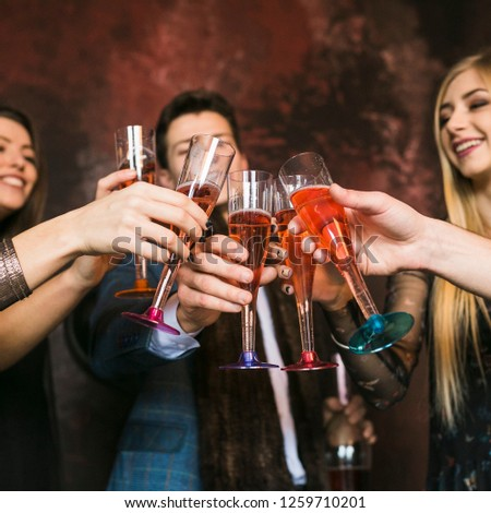 Group of diverse culture friends cheering with red wine in trendy winery bar - Happy people drinking and having fun pub restaurant after work - Party and nightlife concept - Focus on close up hands #1259710201