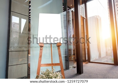 Wooden board with blank poster, display floor stand in banner advertising concept in entrance of hotel. Mock up. Interior design decoration background