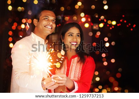 Happy Indian couple celebrating a festival and lighting bengal fire #1259737213