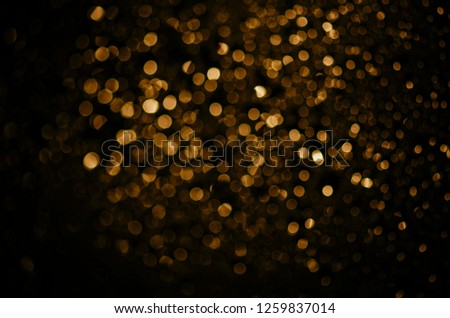 Blur neon gold light circle background. Sparkling firework bokeh dots in retro film filter style. Luxury and classy new year and christmas party textured backdrop. Blurry golden dust particles.
