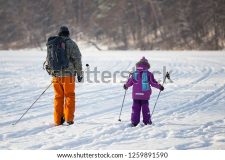 Dad and daughter go cross-country skiing. View from the back. Sunny day. In the background is a forest. #1259891590