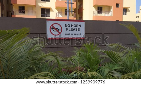 No Horn Please Sign Board with Plants and Wall near Hospital and Schools Royalty-Free Stock Photo #1259909776