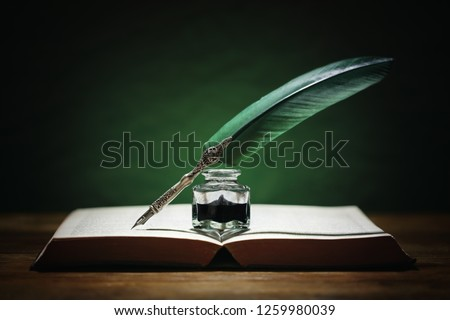 Quill pen and inkwell resting on an old book with green background concept for literature, writing, author and history #1259980039