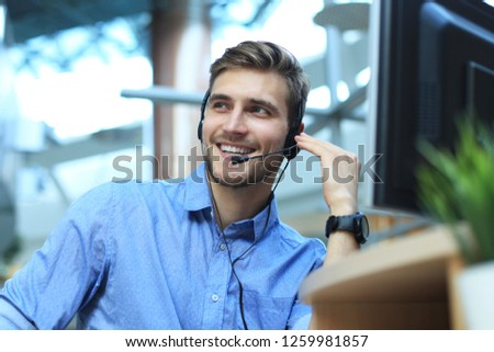 Smiling friendly handsome young male call centre operator. #1259981857