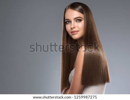 Beautiful model girl with shiny brown and straight long hair. Keratin  straightening. Treatment, care and spa procedures. Smooth hairstyle Royalty-Free Stock Photo #1259987275