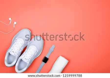 Top view of white sport shoes (sneakers) with smart watch (activity tracker), earphones (headphones) and towel on coral color background. Losing weight and sport trendy  concept. Flat Lay. Copy space. #1259999788