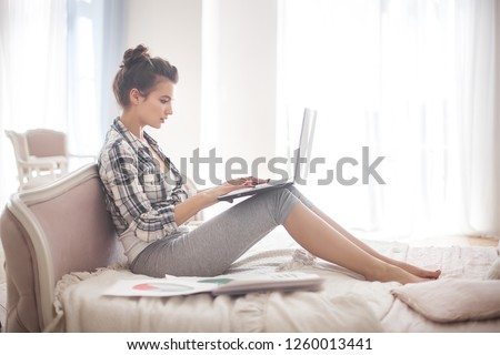 Young woman woking at the computer at home. Female typing. Freelancer working at laptop. Distant job.