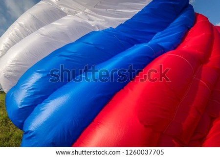 Abkhazia Sukhum Babushara 09.14.2017  Canopy of colorful parachute in blue sky. A background with an abstract view of a colorful parachute. Parachute jumps. Active life style. #1260037705