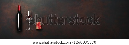Bottle of wine with wineglass and gift box on rusty brown background. Panoramic top view with copy space for your text. #1260093370