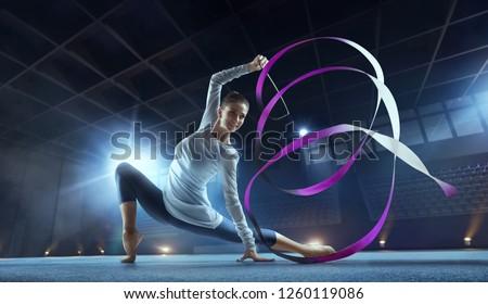 Beautiful rhythmic gymnast in professional arena. #1260119086