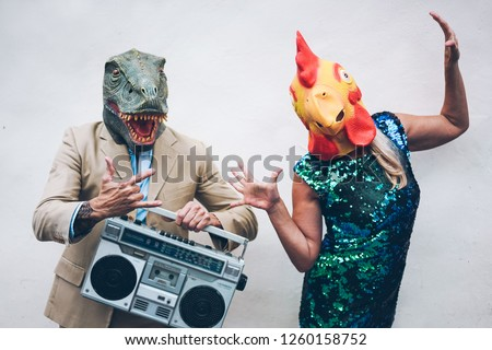 Crazy senior couple dancing for new year's eve party wearing t-rex and chicken mask - Old trendy people having fun listening music with boombox stereo - Absurd and funny trend concept - Focus on faces #1260158752