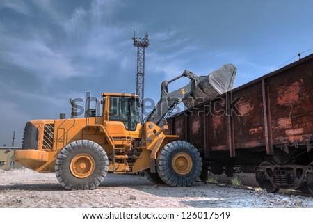 Wheel loader excavator with backhoe unloading clay #126017549