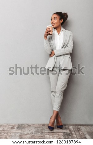 Full length portrait of a confident african business woman wearing suit standing over gray background, holding cup of takeaway coffee Royalty-Free Stock Photo #1260187894