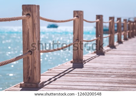View at the sea from the wooden pier with posts and ropes with sparkling sea water Royalty-Free Stock Photo #1260200548