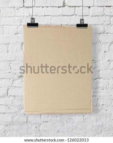 yellow cardboard poster on brick wall