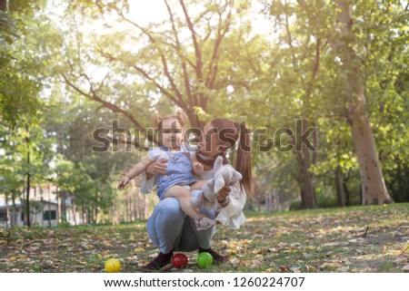 Mother showing daughter her toys in park. #1260224707