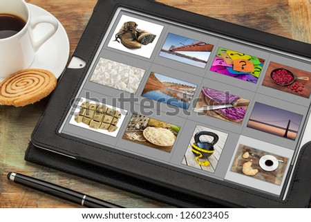reviewing image library (grid of thumbnails) on a digital tablet computer, table with a cup of coffee; all displayed pictures copyright by the photographer