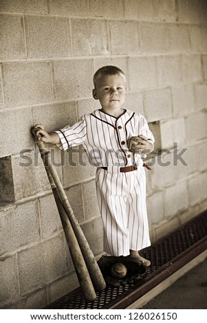 Adorable little boy in an old time baseball uniform.  Special editing to give the photo an old time feel.