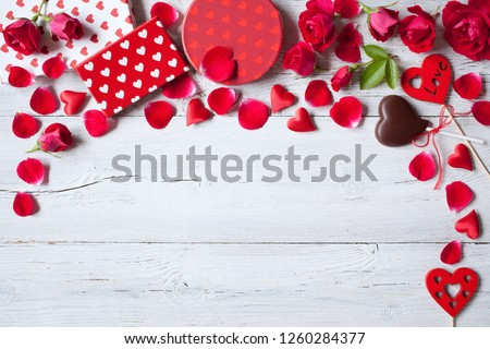 Roses and red hearts on a wooden background and gifts in boxes #1260284377