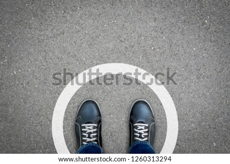 Black shoes standing in white circle on the asphalt concrete floor. Concept of limit, boundary, frame, etc. Royalty-Free Stock Photo #1260313294