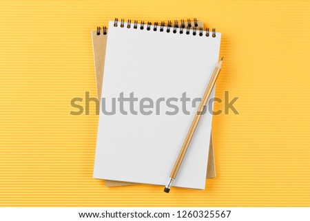 open notebook on corrugated yellow background with pencil top view, spiral notepad with blank sheet, flat lay. school concept, desktop of businessman. #1260325567