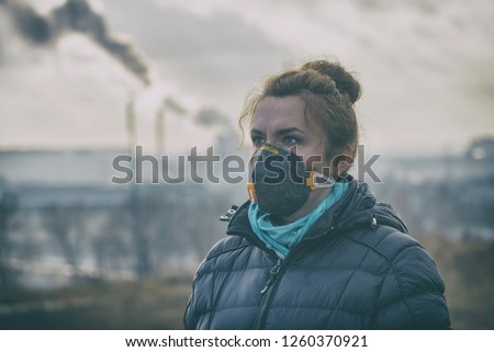Woman wearing a real anti-pollution, anti-smog and viruses face mask; dense smog in air. #1260370921