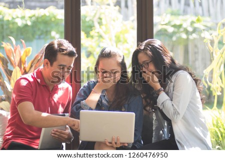 group of happy young man laughing each others while using laptop and tablet pc near windowsill on a sunny day #1260476950