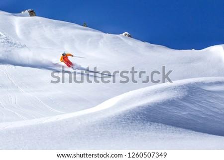 freeride skier skiing downhill through fresh powder snow #1260507349