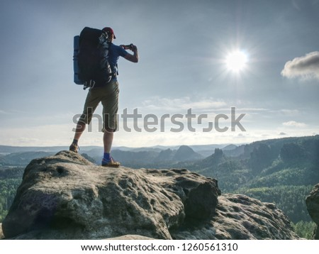 Nature photographer working with camera and tripod on peak of rock. Wild nature park with deep forests in valleys #1260561310