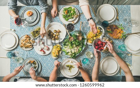 Mediterranean style dinner. Flat-lay of table with salads, starters, pastries over blue table cloth with hands holding drinks, sharing food, top view. Holiday gathering and vegetarian party concept Royalty-Free Stock Photo #1260599962