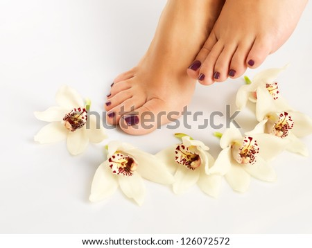 Closeup photo of a female feet with beautiful pedicure after spa procedure on white background #126072572