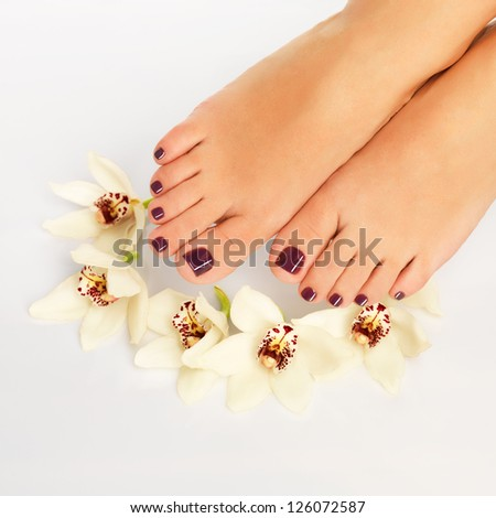 Closeup photo of a female feet with beautiful pedicure after spa procedure on white background #126072587
