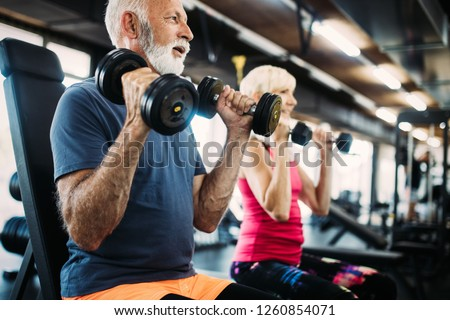 Senior fit man and woman doing exercises in gym to stay healthy #1260854071