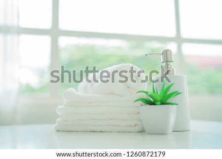 White towels, ceramic soap, shampoo bottle with copy space on blurred living room background. For product display montage #1260872179